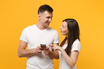 Beautiful young couple friends guy girl in white empty blank t-shirts posing isolated on yellow orange background. People lifestyle concept. Mock up copy space. Using mobile phone, typing sms message.