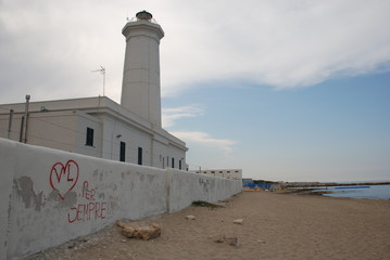 The white lighthouse at San Cataldo on the southern Italian coast. In the foreground, a wall is graffitied