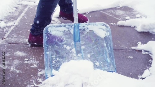 Wall mural Slow motion. Young man shoveling snow from driveway.