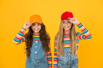 Modern fashion. Kids fashion. Girls long hair wear cap. Cute children wear cap snapback hat. Little girls wearing baseball cap. Matching outfits. Trendy and fancy. Fashion shop. Must have accessory