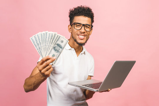 Closeup portrait, young successful african american business man making money from internet, holding cash in hand, laptop in another, isolated over pink background.