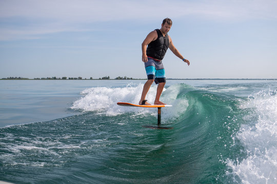 Man wake surfing with foil board.