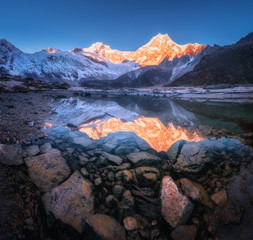Wall Mural - Snowy mountain with illuminated peaks is reflected in beautiful lake at sunrise. Panoramic landscape with lighted rocks, blue sky, pond, stones in water at dawn. Himalayan mountains in Nepal. Nature