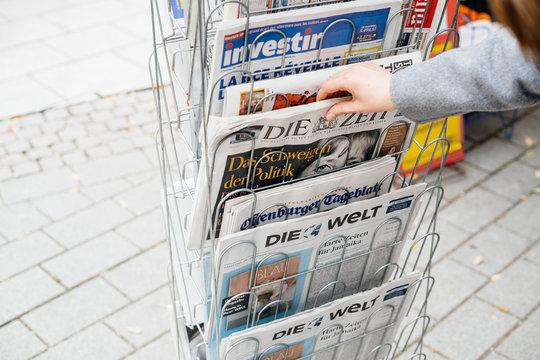 STRASBOURG, FRANCE - OCT 28, 2017: Woman reading buying German Die Zeit newspaper at press kiosk featuring Angela Merkel and tilte The Silenece of Politics