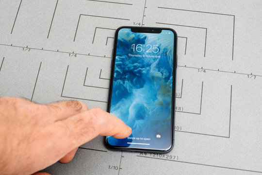 PARIS, FRANCE - NOV 9, 2017: Male hand touch selecting New Apple iPhone X 10 smartphone screen after unboxing and unlocking swipe out