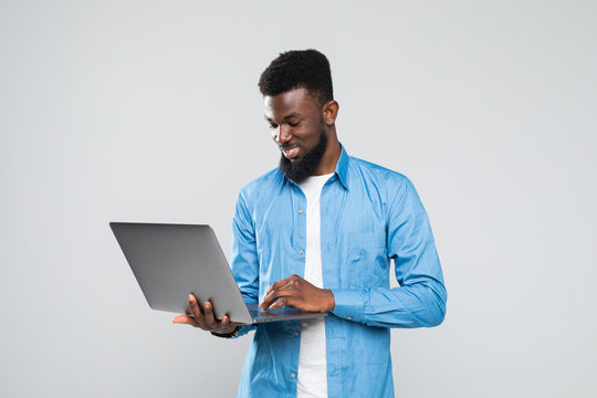 Young smiling african man standing and using laptop isolated over gray background