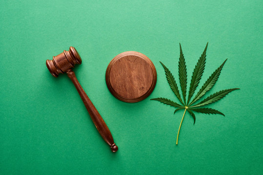 top view of green marijuana leaf with wooden gavel on green background