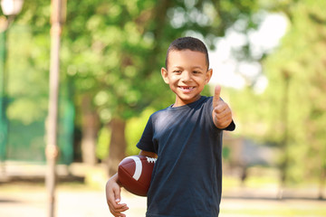 Cute little African-American boy with rugby ball showing thumb-up gesture in park Fototapete
