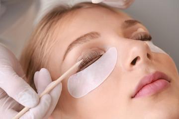 Young woman undergoing procedure of eyelashes lamination in beauty salon, closeup Fototapete