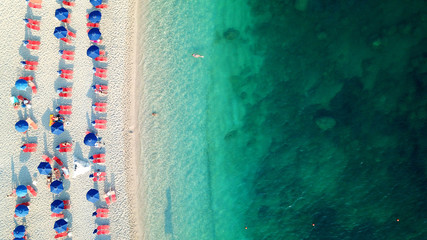 Aerial top view photo of sun beds and umbrellas in popular tropical paradise deep turquoise Mediterranean sandy crowded beach
