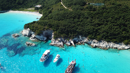 Aerial drone photo of tropical paradise turquoise beach of Voutoumi with sail boats docked in island of Anti paxos, Ionian, Greece