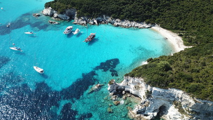 Aerial drone photo of tropical paradise turquoise beach of Voutoumi with sail boats docked in island of Antipaxos, Ionian, Greece Wall mural