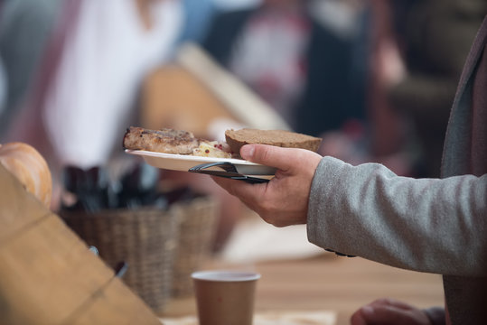 Men's hands take a plastic plate of food. The concept of helping the homeless and the needy.