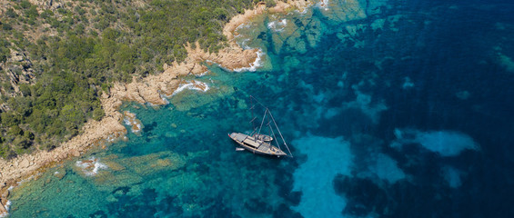 Wall Mural - View from above, stunning aerial view of a luxury sailboat floating on a beautiful turquoise sea that bathes the green and rocky coasts of Sardinia. Emerald Coast (Costa Smeralda) Italy