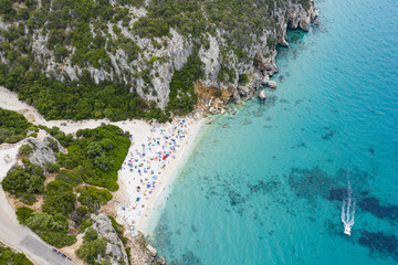 Fototapete - View from above, stunning aerial view of a beautiful beach full of beach umbrellas and people sunbathing and swimming on a turquoise water. Cala Gonone, Sardinia, Italy.