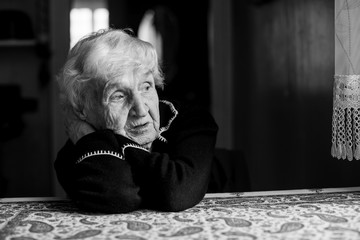Lonely sad old woman. Black and white photo.