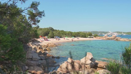 Fototapete - Stunning view of a beautiful beach with tourists sunbathing and swimming on a turquoise clear sea, Emerald coast (Costa Smeralda) Sardinia, Italy.