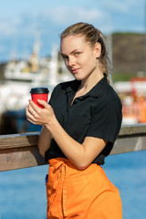A young female waitress holding a disponsable paper cup of coffee looking camera outdoors.