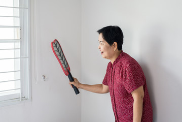 Asian senior woman using mosquito swatter at home,Female with mosquito electric net racket in bedroom