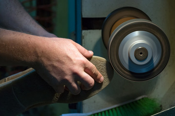 Male shoemaker hands grinding and shaping a sole in his workshop, close up.