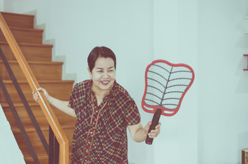 Female with mosquito electric net racket at house,Senior woman using mosquito swatter at home