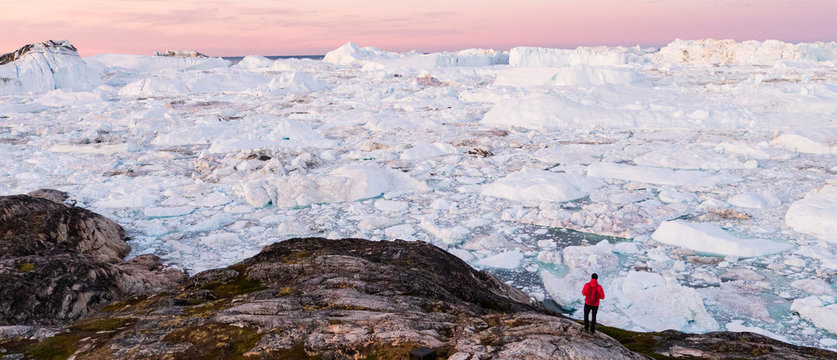 Global warming - Greenland Iceberg landscape of Ilulissat icefjord with giant icebergs. Icebergs from melting glacier. Arctic nature heavily affected by climate change. Person tourist looking at view