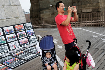A tourist with a pacifier over his mouth stands next to his children as he takes a picture of his wife on Brooklyn bridge in New York