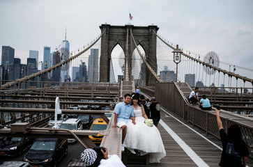 Shin and Miki from Japan are photographed by a photographer on Brooklyn bridge after getting married at Riverside church in New York