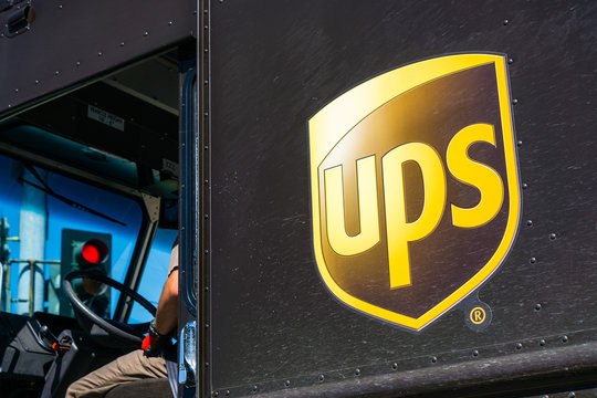April 19, 2018 Santa Clara / CA / USA - Close up of UPS logo printed on a delivery truck; partial view of the driver sitting at the wheel, waiting at a red traffic light in south San Francisco bay