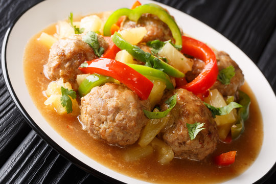 Meatballs cooked with fresh pineapples and vegetables in a sweet and sour sauce closeup on a plate. horizontal