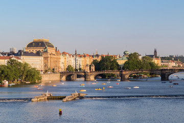 View of the Legion Bridge, National Theatre and other old buildings and people on pedal boats on the Vltava River in Prague, Czech Republic, on a sunny day.