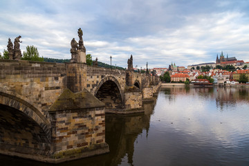 View of the empty Charles Bridge (Karluv most) over Vltava River, Mala Strana District (Lesser Town) and Prague (Hradcany) Castle in Prague, Czech Republic, on a cloudy day.