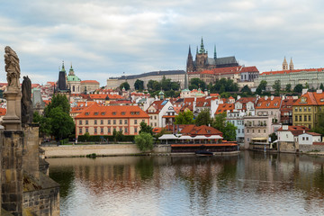View of statues on the Charles Bridge (Karluv most), Mala Strana District (Lesser Town), Prague (Hradcany) Castle and St. Vitus Cathedral in Prague, Czech Republic, on a cloudy day.