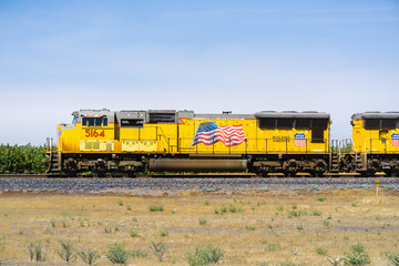 July 17, 2018 Madera / CA / USA - Union Pacific train engines displaying the American flag travelling on the side of the highway
