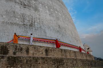 Monks placing a sash around a stupa in Anuradhapura, Sri Lanka