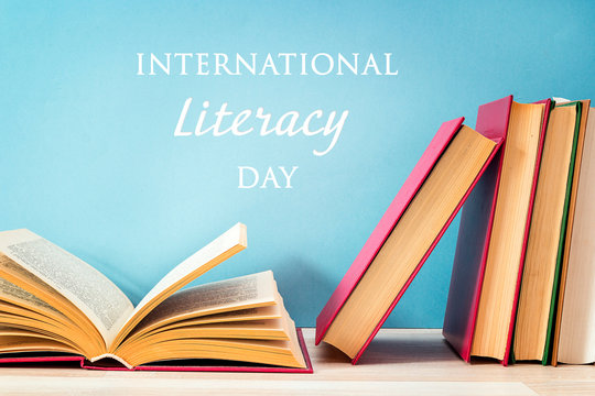 International Literacy Day concept with stack of books on a blue background.