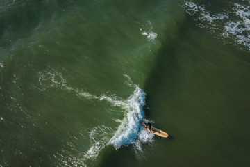 Aerial view on surfer in the sea, surfer catching waves in baltic sea.