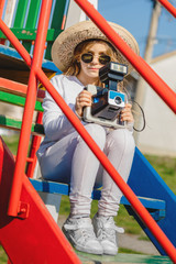 Young girl with old vintage polaroid camera at playground. Young little hipster girl with hat and camera. Creative kids concept.