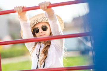 Young fashion girl with hat and sunglasses at playground