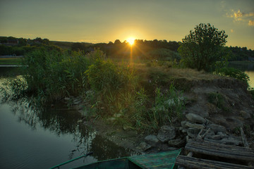 Sunset over the кшмук in the village. View from a wooden bridge