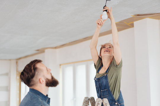 Young woman changing a light bulb on a ladder