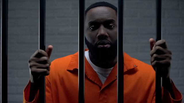 African-american male prisoner holding bars and looking to camera, imprisonment