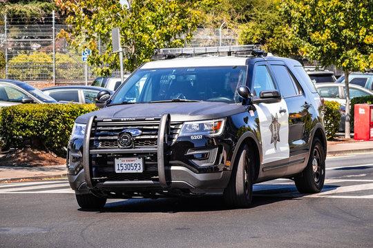 July 26, 2019 Palo Alto / CA / USA - Police car driving on the street, close to downtown Palo Alto, San Francisco bay area