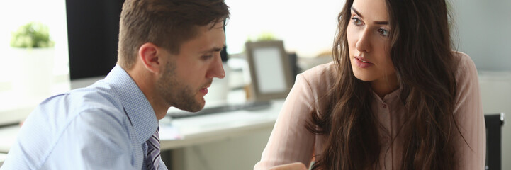 Businessman and businesswoman confer in office