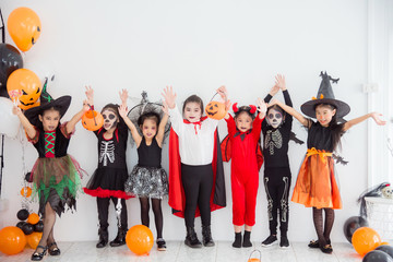 Group of asian children in halloween costume and makeup standing in a row and raising hands up. Wall mural