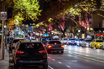 A downtown city street in Melbourne Australia at night, showing city lights, traffic and tram tracks