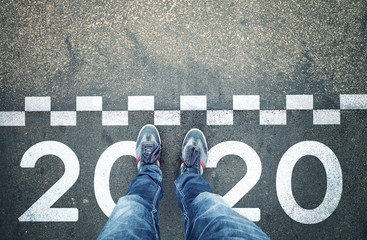 Man stands in front of a start New Year 2020 sign painted on asphalt city street. Point of view perspective used.