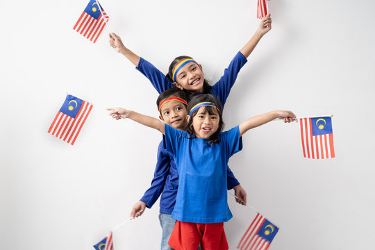 cute kids holding malaysian flag over white background. malaysia independence day
