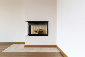 Detail of fireplace with wooden logs and white wall
