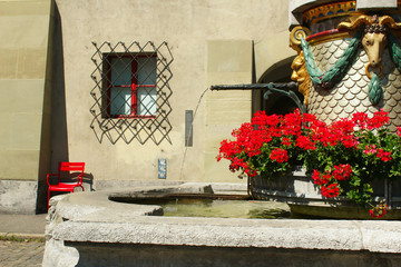 Fountain with water and red flowers at the ancient square Münsterplatz near the cathedral in Bern, Switzerland, summer 2019